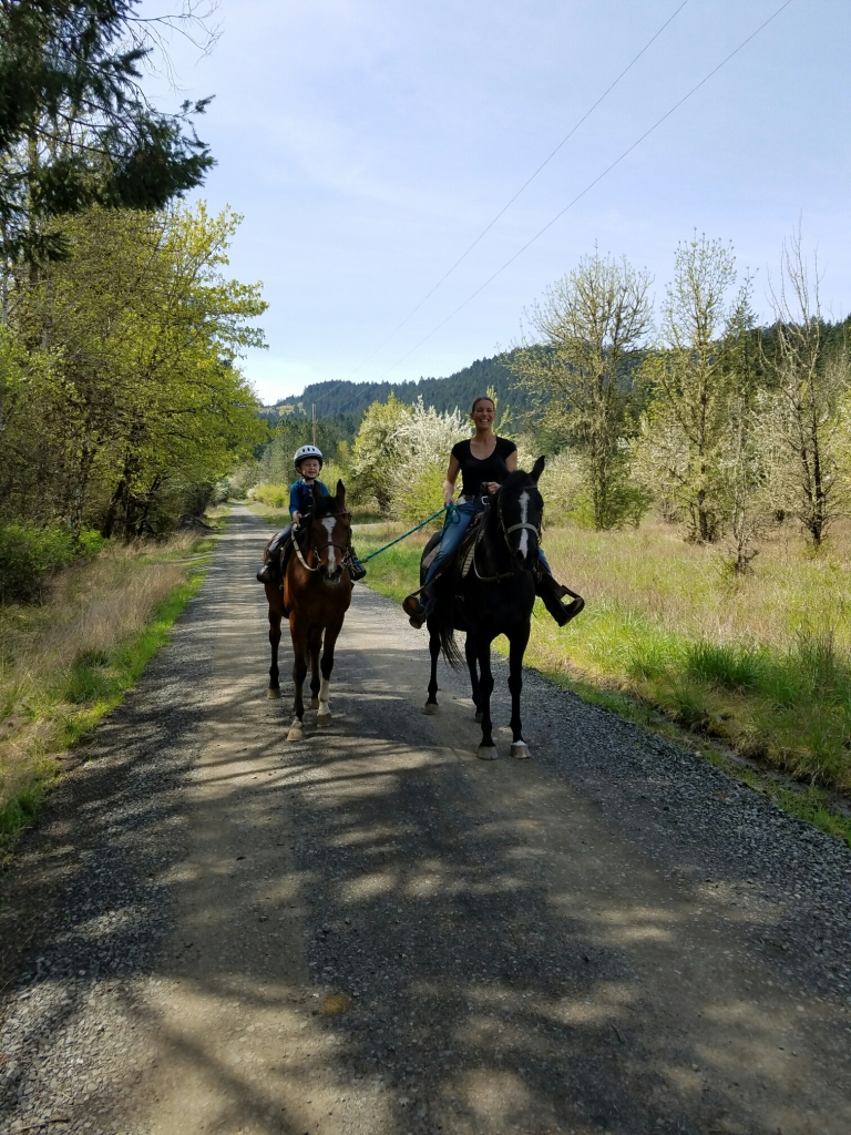 Trainer and young rider each riding on the trail
