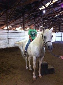 young rider preparing to ride bareback on veteran lesson horse