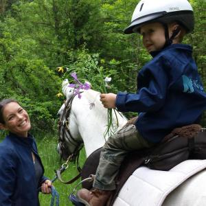 Kate Halle leads young rider on trail and they stop to pick flowers