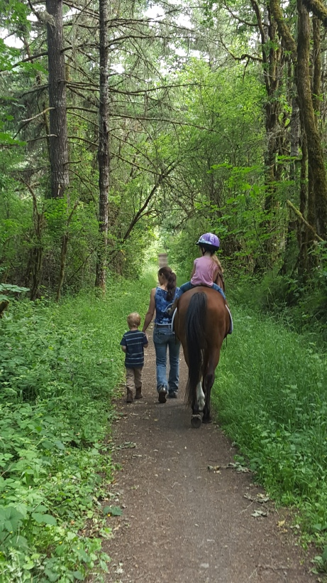 Horse trainer assisting two children riding on the trail