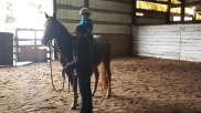 Trainer instructing young rider in the arena
